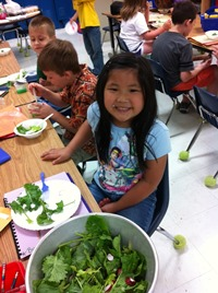 Photo of students trying lettuce from garden